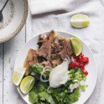 składniki na zupę pho, gotowana wołowina, świeże zioła, chili i limonka
