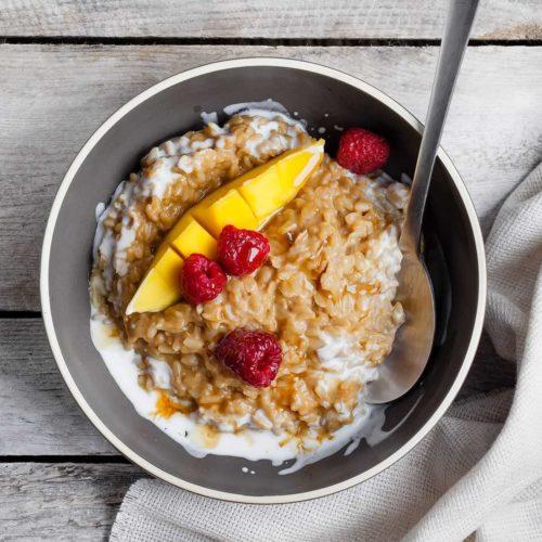 Brązowy ryż z mango, malinami i śmietanką kokosową. Pomysł na zdrowe śniadanie z ryżu z owocami.